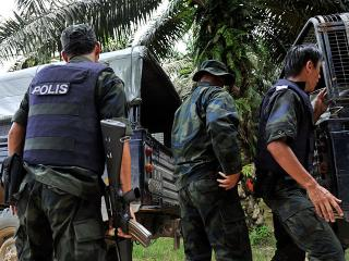 Malaysian police escort dead comrades killed by mortar fire